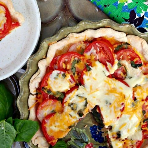 Fresh savory tomato pie topped with cheese, garlic and basil - The Foodie Affair