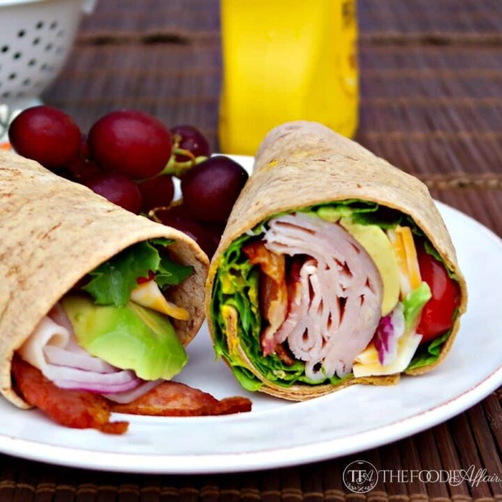 Turkey wrap sandwich on a white plate with grapes