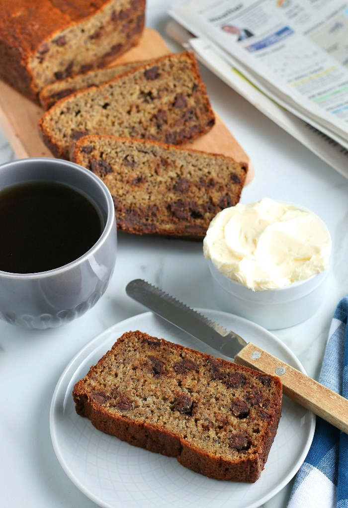 This image shows the finished easy banana bread with chocolate chips recipe served with coffee and butter.