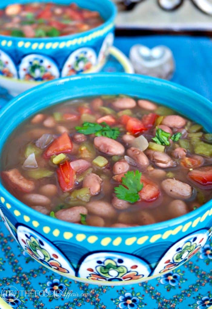 Tasty Mexican Pinto Beans slow cooked with flavorful spices and fresh chopped tomatoes. Serve this as a main dish or a side to your favorite Latin meal! The Foodie Affair
