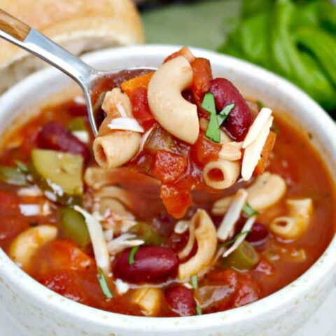 A cream bowl full of minestrone soup