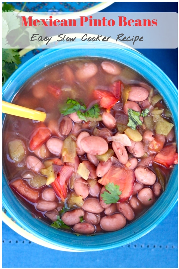 Tasty Mexican pinto beans made in a crock pot with flavorful spices like cumin, oregano, and fresh chopped tomatoes. Serve this as a main dish or a side to your favorite Latin meal! #slowcooker #crockpot #beans #Mexican