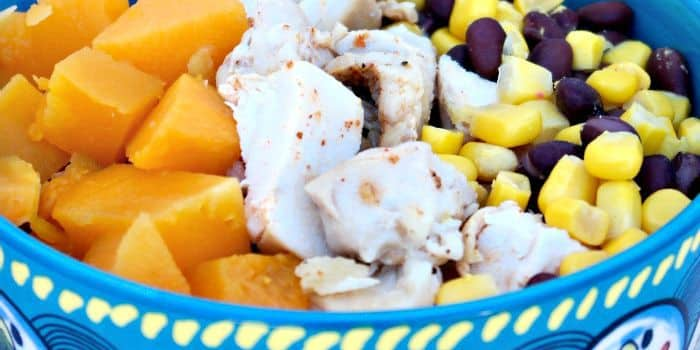 Healthy Quinoa Burrito Bowl layered with Butternut squash, black beans, corn and chicken. topped with a yogurt salsa Ranchera sauce. The Foodie Affair