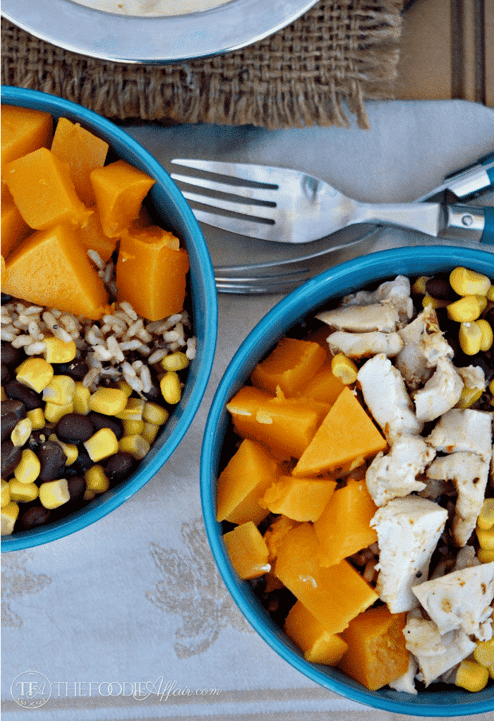 Healthy Quinoa Burrito Bowl layered with roasted butternut squash, black beans, corn and chicken. topped with a yogurt salsa Ranchera sauce. The Foodie Affair