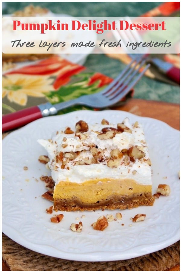 Light and airy pumpkin delight dessert is three layers of delicious Fall flavors: gingersnap crust, creamy pumpkin filling with cream cheese, and fresh whipped cream all topped with chopped pecans! #dessert #fall #pumpkin #partyidea #realingredients #thefoodieaffair