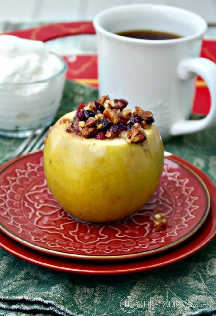 red plate with a stuffed baked apple with coffee in the background