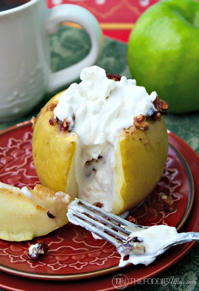 stuffed baked apples topped with whipped cream on a red plate