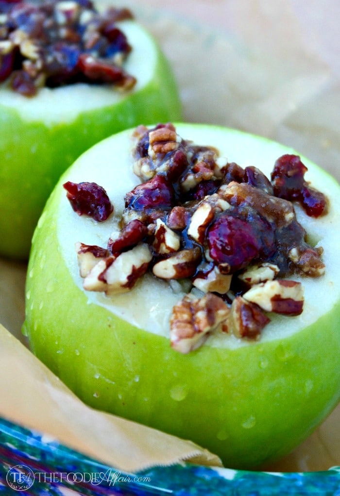 stuffed baked apples are filled with chopped pecans, cranberries, brown sugar in a baking dish