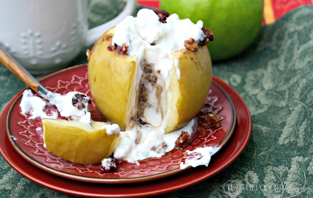sliced open baked apple with melted whipped cream on a red plate