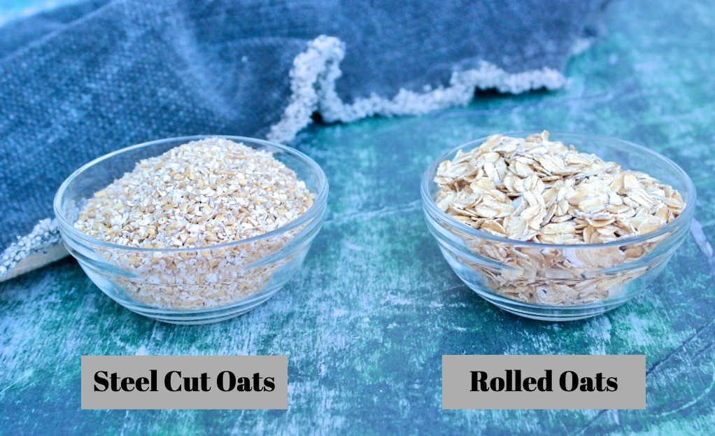 Two types of uncooked oatmeal, rolled and steel oats in a small glass bowl.