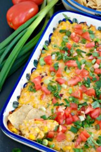 This Hot Cheesy Corn Dip is baked with a creamy yogurt base folded with cheese, sweet corn, green chilis, and then topped with fresh vegetables! Easy and delicious! The Foodie Affair