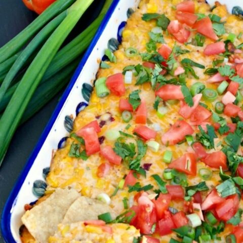 Corn dip in a casserole dish topped with diced tomatoes and onions