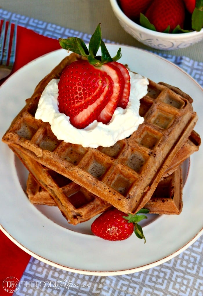 chocolate waffle recipe with freshly made waffles on a white plate with whipped cream and strawberries