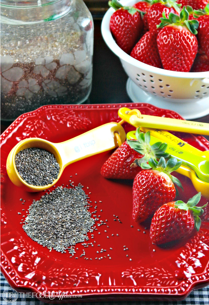 Strawberry Chia Jam ingredients : seeds and fresh berries on a red plate