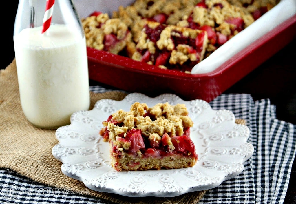 Strawberry oat bars on a white plate with a glass of milk on the side