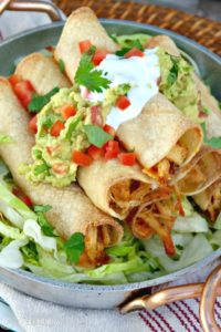 Baked Chicken Taquitos filled with seasoned shredded chicken and cheese comes together quickly when baked in the oven instead of fried. Add your favorite toppings and enjoy at your next fiesta! The Foodie Affair