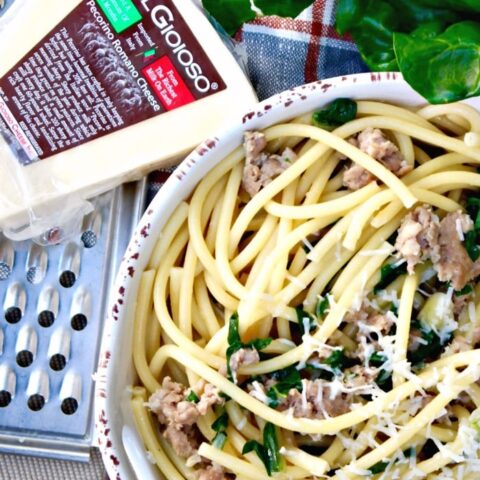 Bucatini pasta with Sausage and Kale in a serving dish.