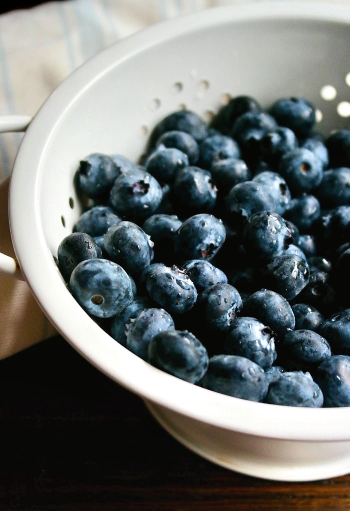 fresh blueberries in a white colander