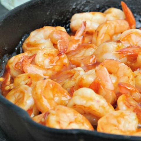 A cast iron skillet filled with tequila shrimp ready to be served
