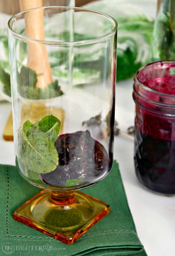 blueberry sauce at the bottom of a glass for blueberry mojito recipe