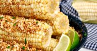 Easy Mexican Style Corn on the Cob topped with plenty of melted butter, chili powder, cotija cheese, salt and fresh lime juice.