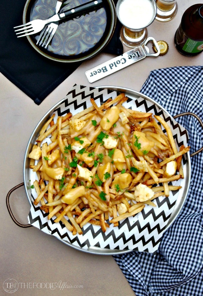 French-Canadian Poutine dish is made of French fries, cheese curds and light brown gravy! Flavorful and easy to make when you use pre-made fries!