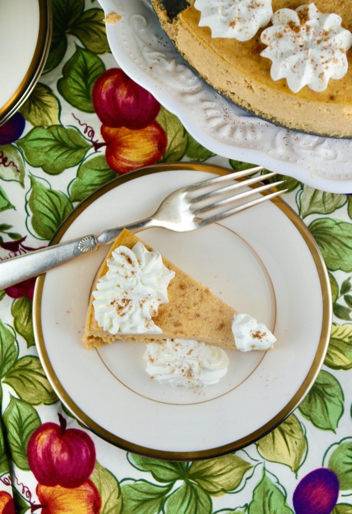 Overhead photo of a slice of pumpkin cheesecake on a cream colored plate