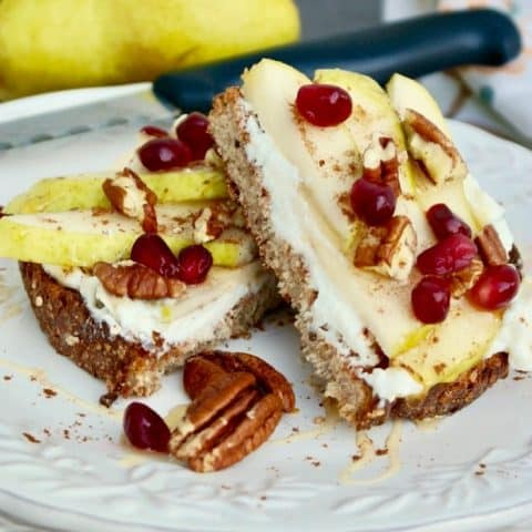Ricotta toast with pears and pecans on a white plate