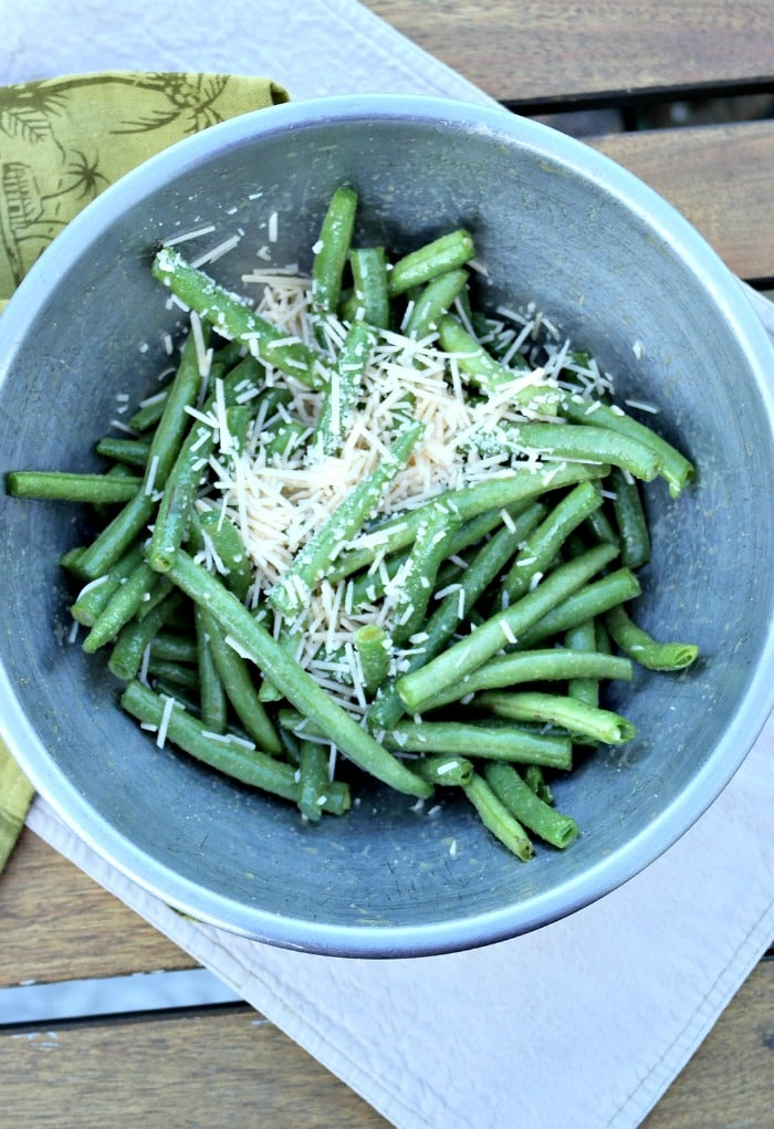 Green beans in a bowl seasoned with parmesan and garlic.