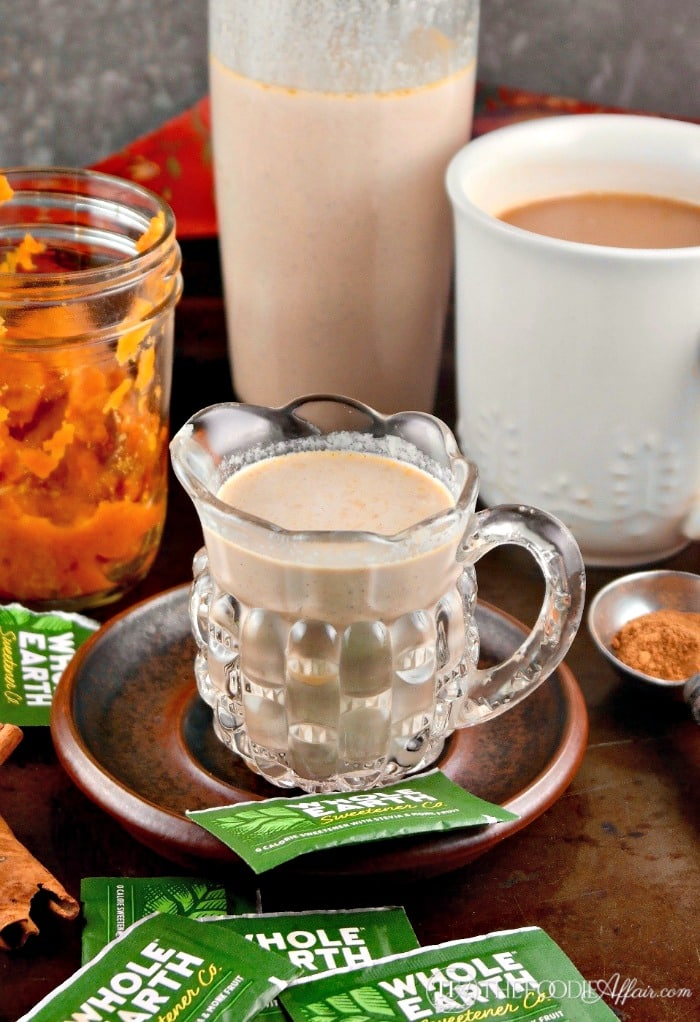 pumpkin spice coffee creamer in a clear decanter with a white coffee cup filled with coffee on the side