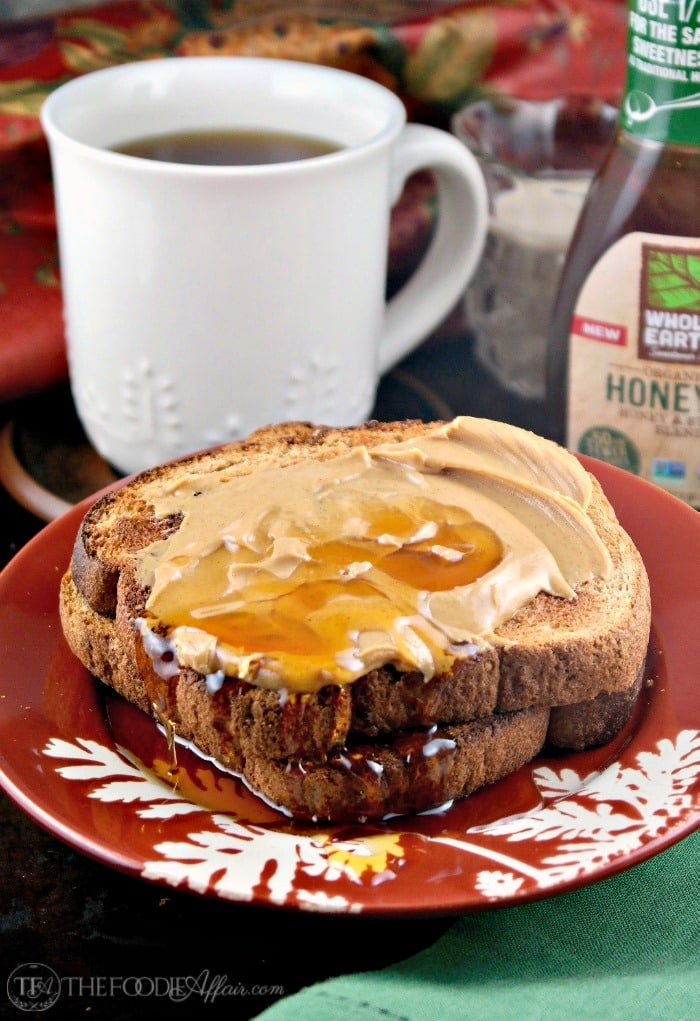 Cup of coffee in a white mug with toast topped with peanut butter and honey