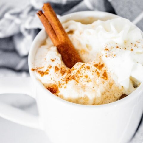 A white mug with coffee topped with whipped cream.