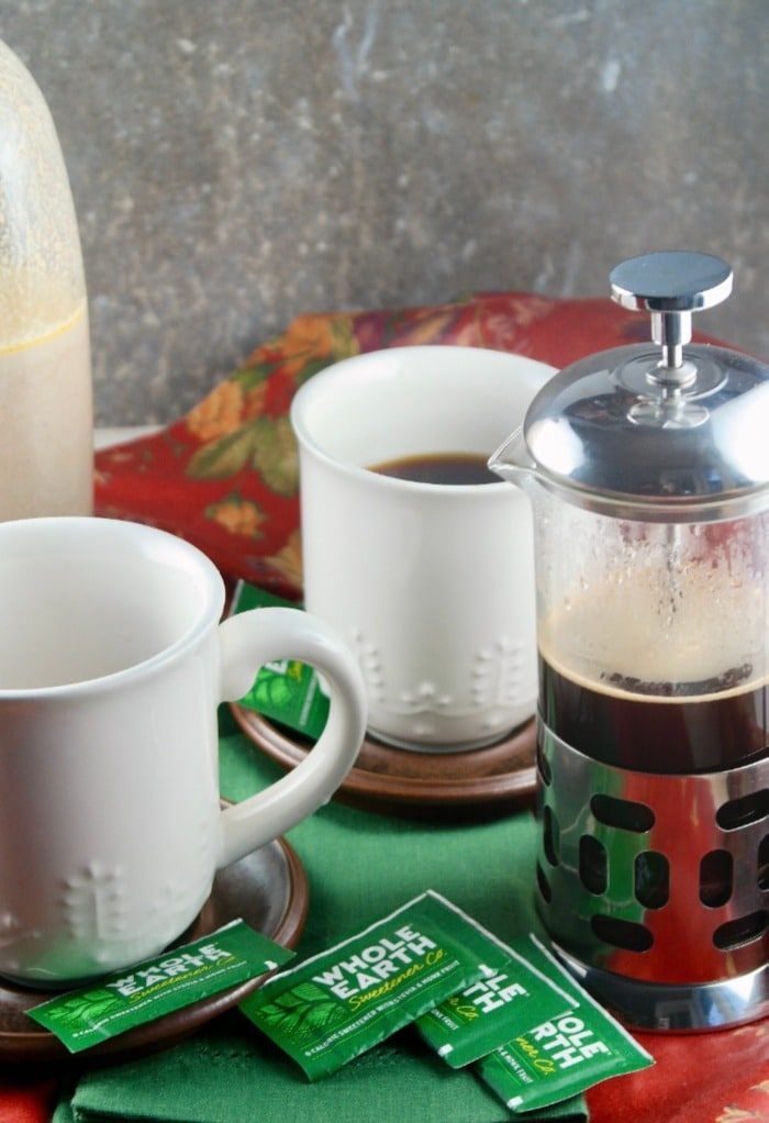 Fresh coffee made in a French press with white coffee cups on the side.