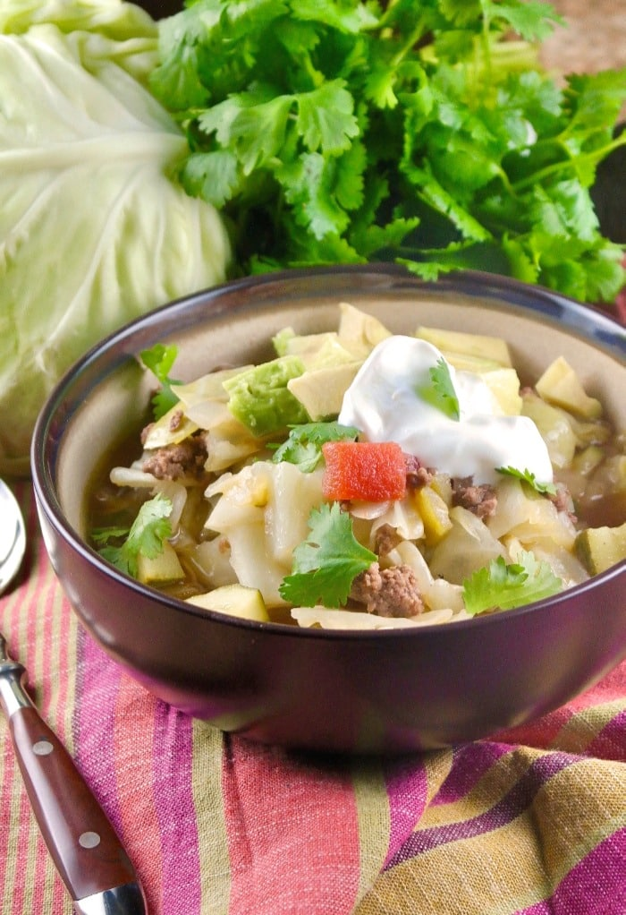 Low carb Mexican beef cabbage soup topped with avocado and crema for a delicious complete meal! #30minute #dinner #lowcarb #ketodiet #Mexican | www.thefoodieaffair.com
