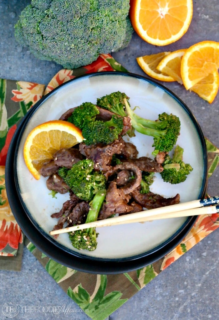 Overhead view of beef and broccoli stir fry with sliced oranges on the side of a cream plate with black rim.