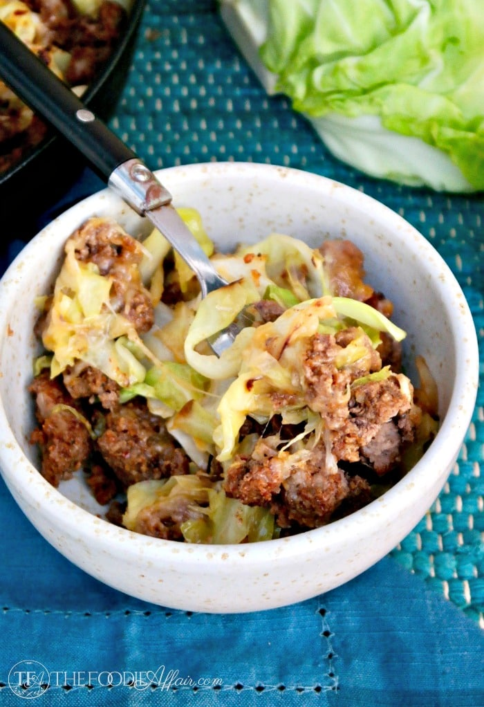 Tex Mex cabbage beef skillet in a cream bowl with blue napkin