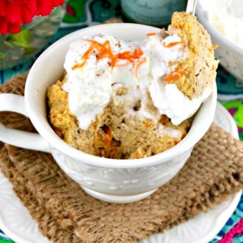 Low carb mug cake with whipped cream and shreds of carrots on top.