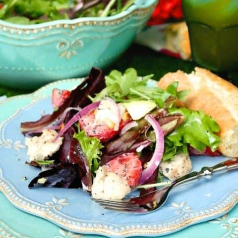 A light blue plate with strawberry avocado chicken salad on a blue napkin