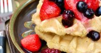 Low carb waffles on a plate topped with berries