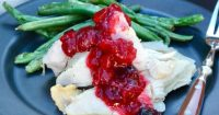 Healthy Cranberry Sauce without sugar topped on slices of turkey on a black plate with green beans #Healthy #CranberrySauce #LowCarb | www.thefoodieaffair.com