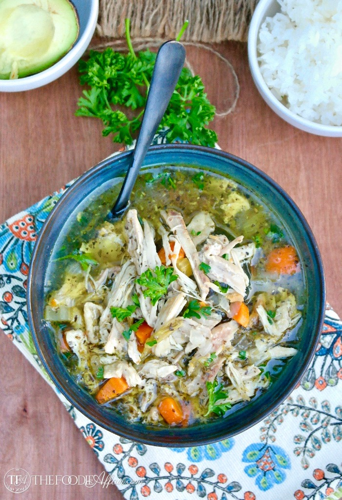 Hearty bowl of instant pot chicken soup with rice and avocado on the side #PressureCooker #EasyRecipe #Soup | www.thefoodieaffair.com