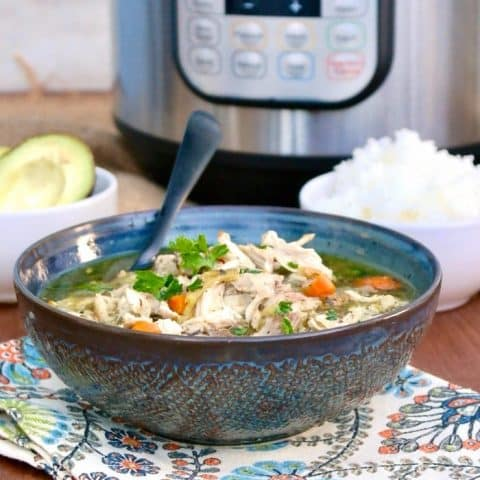 Teal patterned bowl of instant pot chicken soup on a flowered napkin #Chicken #Soup #Instant Pot   www.thefoodieaffair.com
