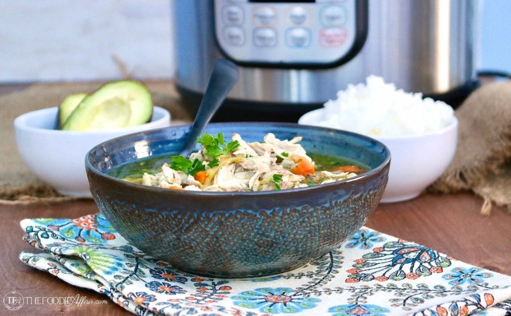 Bowl of chicken soup with a pressure cooker, Instant Pot in the background #Chicken #Soup #InstantPot | www.thefoodieaffair.com