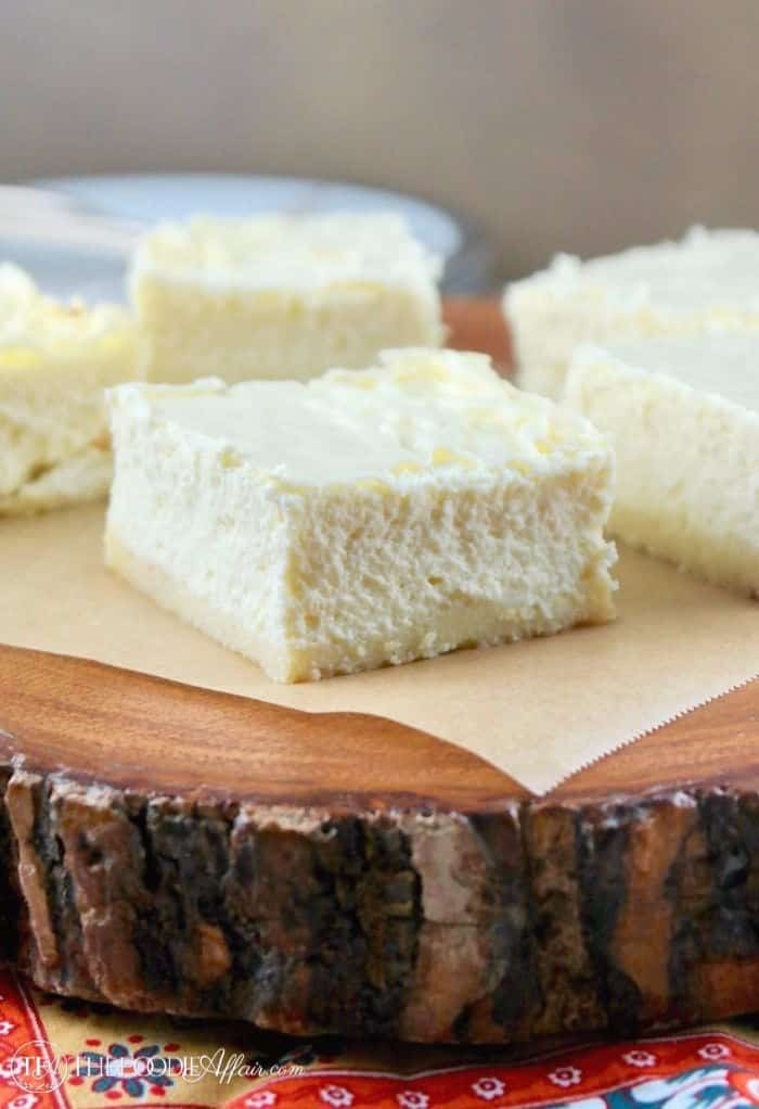 Sugar Free Cheesecake Bars without any topping on a wooden platter #cheesecake #SugarFree #GlutenFree | www.thefoodieaffair.com