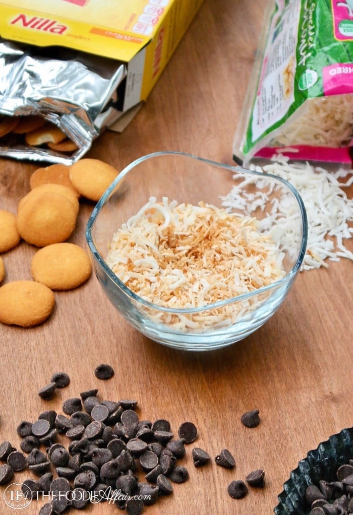 Ingredients for no bake cookies: vanilla wafers, chocolate chips, and coconut flakes lightly browned in a clear bowl #nobake #cookies #Samoas | www.thefoodieaffair.com