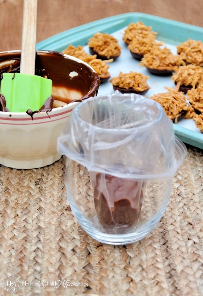 Melted chocolate in a clear glass with plastic baggie for piping melted chocolate over cookies #Cookies #NoBake #Chocolate | www.thefoodieaffair.com
