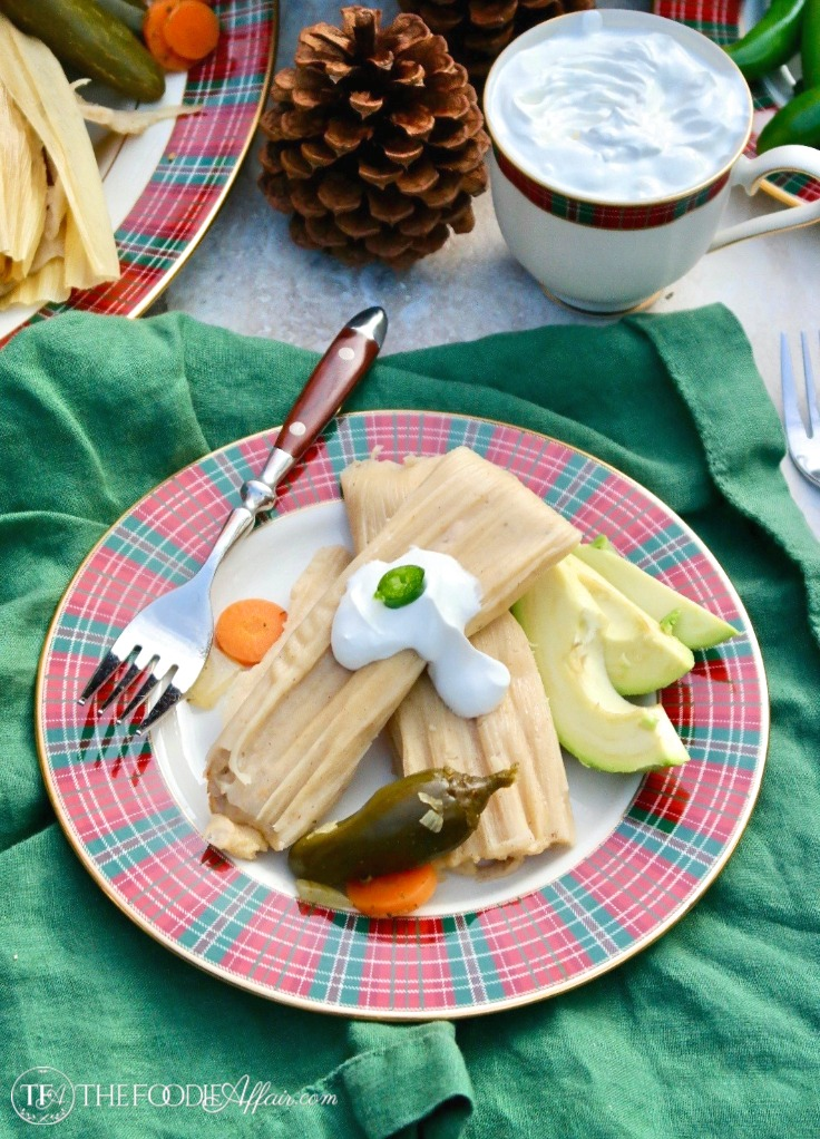 Cooked homemade turkey tamales on a red and green plaid plate topped with sour cream and jalapeños #tamales #recipe #homemade #Mexican | www.thefoodieaffair.com