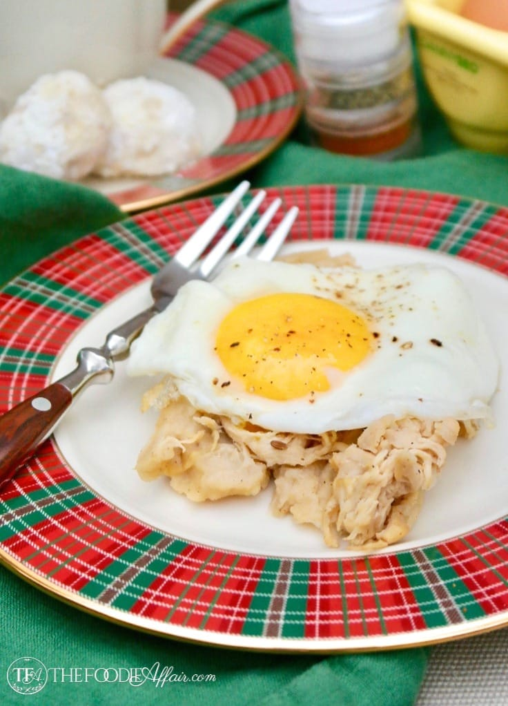Cooked turkey homemade tamale topped with an egg on a red and green plaid rimmed plate #tamale #Mexican #recipe | www.thefoodieaffair.com
