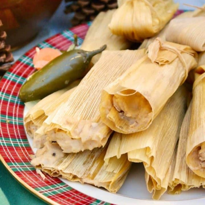 Homemade tamales in corn husk wraps on a plaid platter #tamales #homemade #recipe | www.thefoodieaffair.com