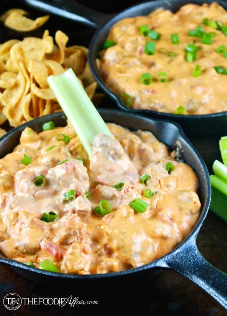 Easy appetizer of sausage queso dip for a crowd. Two mini iron skillet pans filled with cheesy dip with chips and celery sticks #dip #queso #sausage | www.thefoodieaffair.com